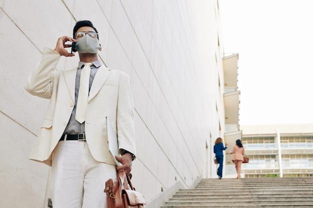 Bel giovane uomo d'affari in abito bianco e maschera medica che scende le scale lasciando l'edificio degli uffici e parlando al telefono con un collega o un partner commerciale