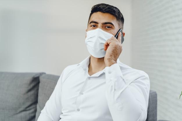 Bel giovane imprenditore con maschera facciale parlando al telefono, ritratto