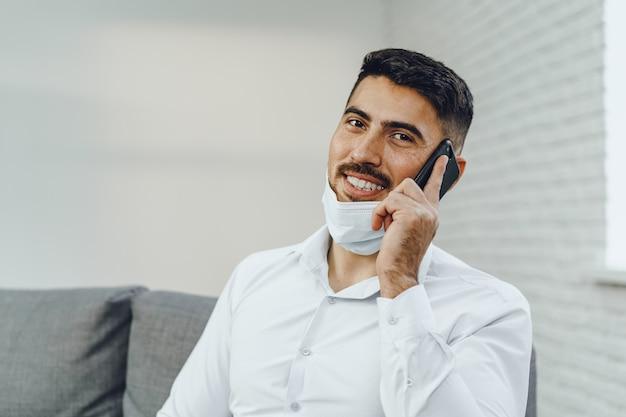 Bel giovane imprenditore con maschera facciale parlando al telefono