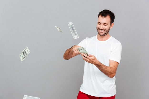 Bel giovane uomo casual che conta soldi su sfondo grigio