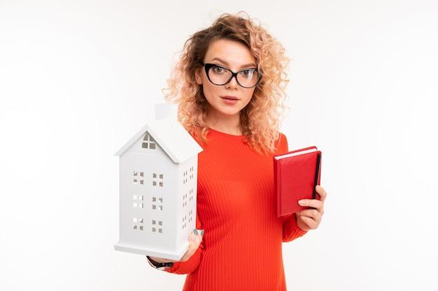Bella giovane femmina caucasica con capelli corti ricci biondi in camicetta rossa vuole comprare una casa, immagine isolata su sfondo bianco