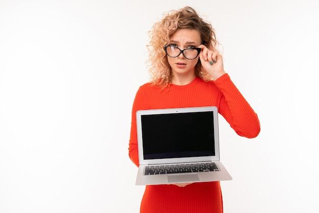 Bella giovane femmina caucasica con capelli biondi ricci corti in camicetta rossa funziona con il computer portatile, immagine isolata su sfondo bianco