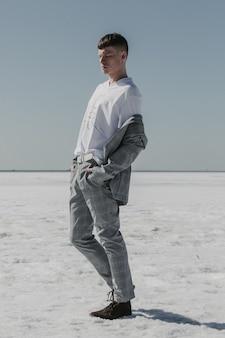 Bel giovane uomo caucasico in posa sull'oceano ghiacciato sotto i raggi del sole.