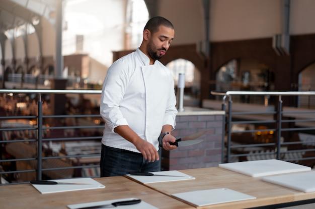 Bel giovane chef etnia africana pone i coltelli sul tavolo di fronte a una master class culinaria. uomo di afro in uniforme del cuoco unico che si prepara per le lezioni di cucina.