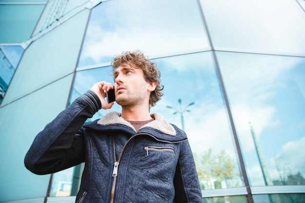 Bel giovane fiducioso attraente ragazzo riccio di successo in giacca nera che parla al cellulare vicino a un moderno edificio di vetro
