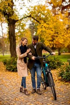 Bella giovane coppia nel parco autunnale con bicicletta elettrica