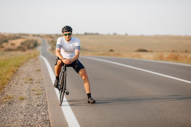 Bel giovane ciclista sul casco protettivo, occhiali e sport outdir avendo una pausa durante la corsa mattutina all'aperto