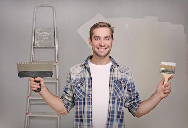 Bel giovane decoratore con spatola e pennello in camera preparata per la riparazione