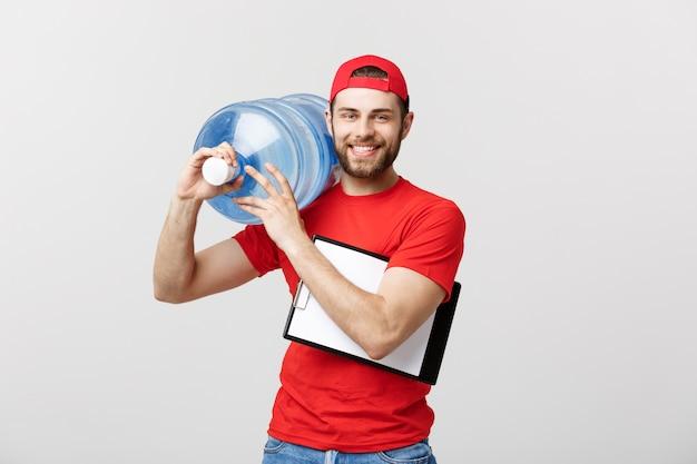 Il giovane fattorino bello in uniforme rossa sta tenendo una bottiglia di acqua