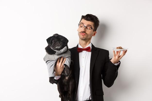 Bel giovane proprietario di cane in abito fantasia che tiene carino pug nero e piatto con cibo animale, in piedi sopra il bianco.