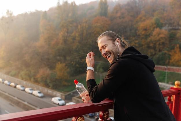 Bel giovane sportivo in forma che ascolta musica con auricolari wireless su un ponte, tenendo in mano una bottiglia d'acqua, ridendo