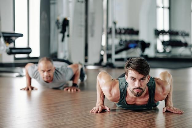Bel giovane istruttore di fitness che mostra metà cobra push up per maturare il cliente in palestra