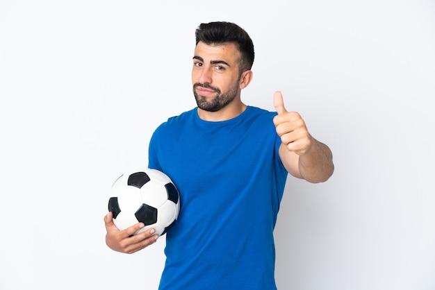 Bel giovane calciatore uomo sopra il muro isolato con i pollici in su perché è successo qualcosa di buono