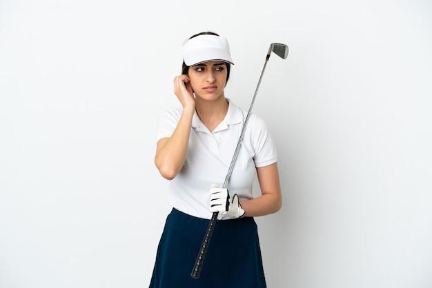 Bel giovane giocatore di golf donna isolata su sfondo bianco frustrato e che copre le orecchie