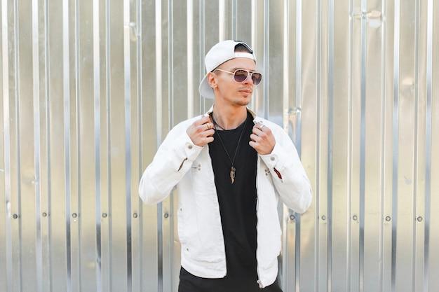 Uomo alla moda giovane hipster bello in occhiali da sole scuri in un'elegante giacca bianca in un berretto da baseball alla moda in una maglietta nera vicino a un muro di metallo grigio in una giornata estiva
