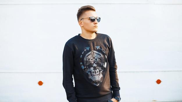 Uomo giovane bello hipster in un abbigliamento elegante nero con un teschio e occhiali da sole su un muro bianco