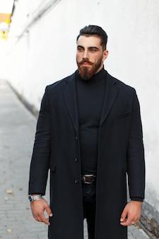 Uomo giovane bello hipster con capelli e barba in vestiti di moda neri con cappotto sulla strada