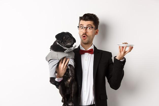 Bel giovane hipster in giacca e occhiali che tiene in mano un simpatico carlino nero e cibo per animali sul piatto, in piedi su sfondo bianco