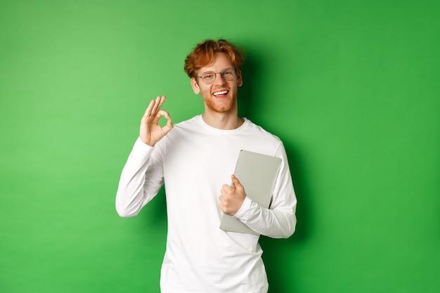 Bel giovane impiegato maschio in bicchieri che mostra segno giusto, tenendo il laptop, in piedi su sfondo verde.