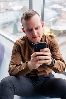 Bel giovane manager maschio è seduto sul pavimento con il telefono vicino alla finestra panoramica. uomo d'affari maschio che lavora a un nuovo progetto