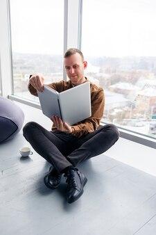 Un bel giovane manager maschio è seduto sul pavimento con il telefono vicino alla finestra panoramica