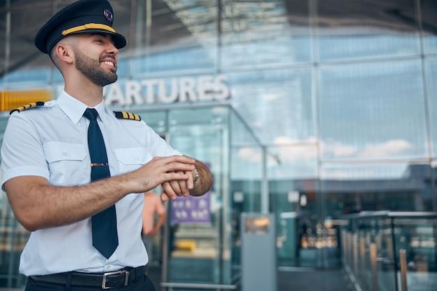 Bel giovane capitano della compagnia aerea in cappello da pilota che tocca l'orologio da polso e sorride mentre aspetta il volo all'aeroporto