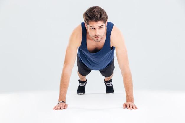 Bel giovane atleta che si allena e fa esercizio di tavola su sfondo bianco white
