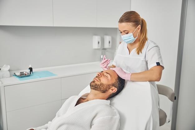 Bel giovane in accappatoio sdraiato sul lettino mentre riceve iniezioni cosmetiche al centro benessere