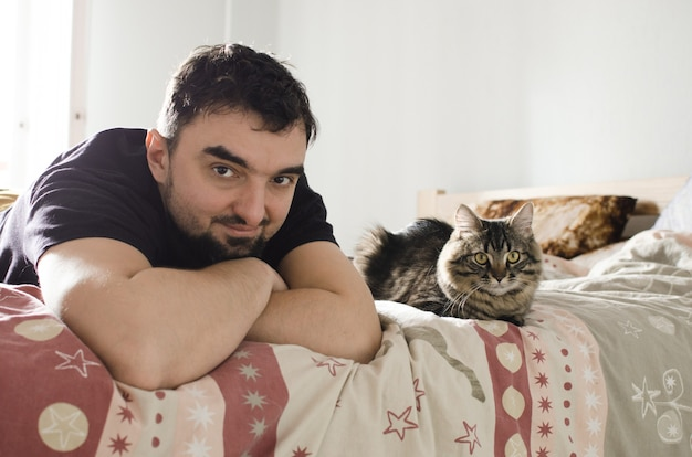 Bel giovane su un letto con simpatico gatto soriano