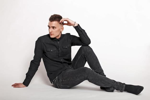Bel giovane in abiti neri, seduto su uno sfondo bianco
