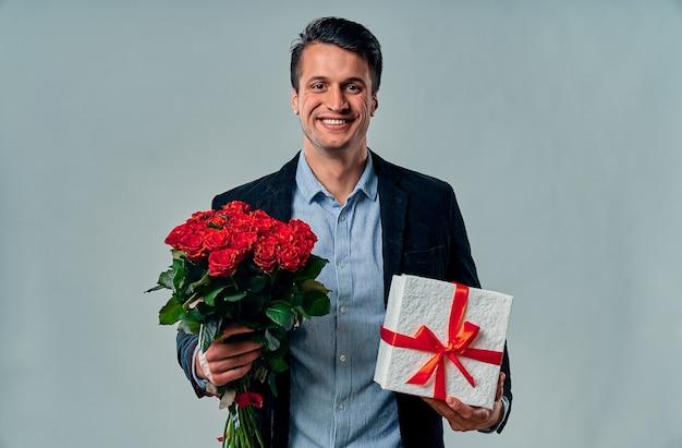 Bel giovane in camicia blu e giacca è in piedi con rose rosse e regalo su grigio.