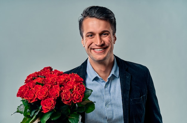 Bel giovane in camicia blu e giacca è in piedi con rose rosse su grigio.