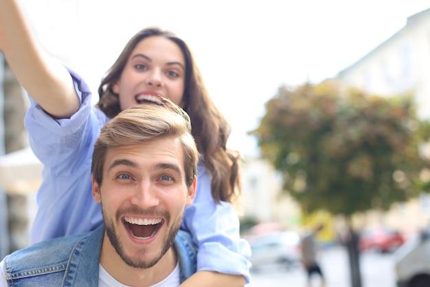 Bel giovane che porta una giovane donna attraente sulle spalle mentre trascorre del tempo insieme all'aperto.