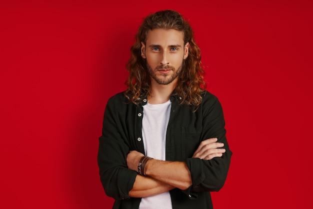 Bel giovane in abbigliamento casual che guarda la macchina fotografica e tiene le braccia incrociate mentre sta in piedi contro il muro rosso red
