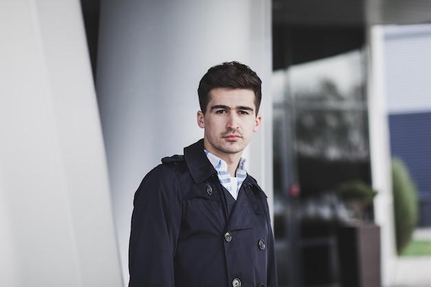Bel giovane uomo in cappotto su urbano. uomo d'affari