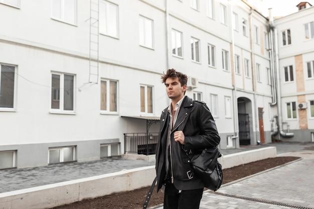 Bel giovane in una giacca di pelle alla moda con un elegante zaino nero con un'acconciatura alla moda cammina per strada vicino a case d'epoca. ragazzo attraente hipster americano in una passeggiata in una giornata di primavera.