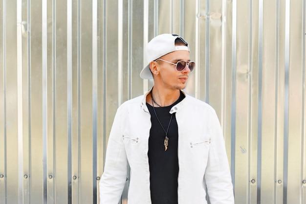 Bel giovane in una giacca alla moda con un berretto da baseball bianco in occhiali da sole vicino al muro di metallo