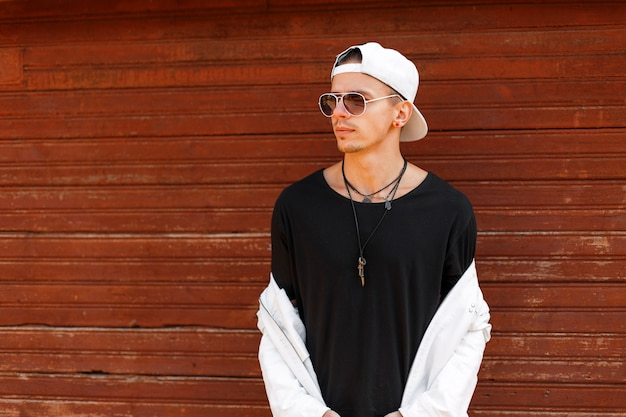 Bel giovane in abiti bianchi alla moda e maglietta nera con un berretto da baseball bianco in occhiali da sole vicino alla parete di legno