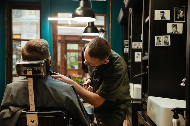 Bel giovane che ottiene taglio di capelli barba dal parrucchiere mentre è seduto in poltrona al barbiere.