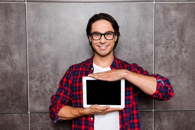 Bel giovane con gli occhiali che mostra lo schermo della tavoletta digitale