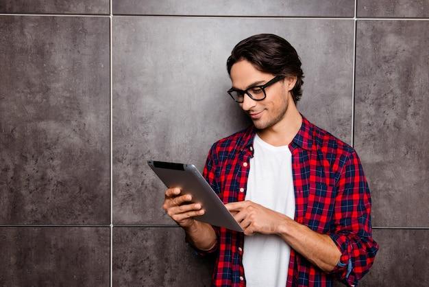 Bel giovane con gli occhiali utilizzando la tavoletta digitale