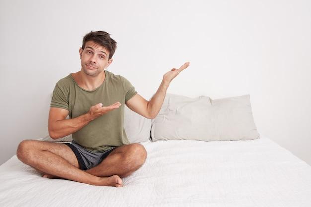 Bel giovane con una maglietta verde seduto sul suo letto a doppia faccia nella sua stanza che punta di lato per presentare pdocutos o testi.