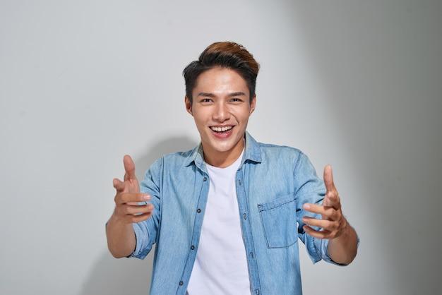 Bel giovane su sfondo grigio guardando la fotocamera. ritratto di ridere giovane con le mani in tasca appoggiata contro il muro grigio. ragazzo felice sorridente.