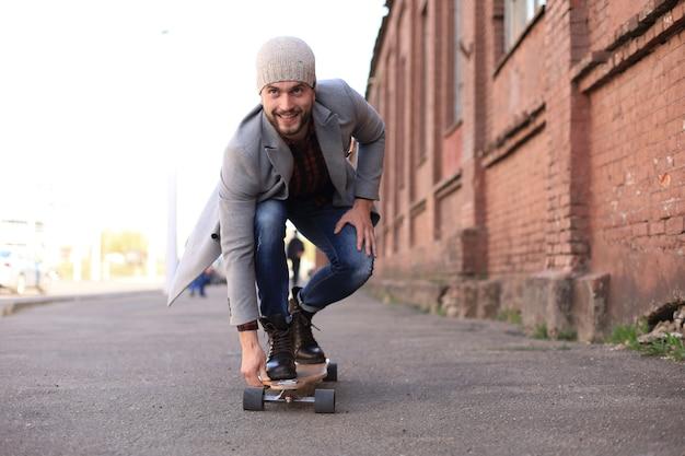 Bel giovane in cappotto grigio e cappello su longboard per strada in città. concetto di skateboard urbano.