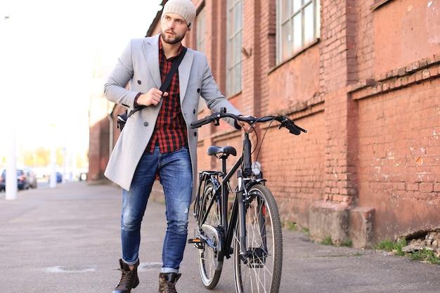 Bel giovane in cappotto grigio e cappello che spinge la sua bici lungo una strada della città.