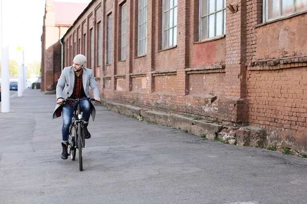 Bel giovane in cappotto grigio e cappello in sella a una strada in bicicletta in città.