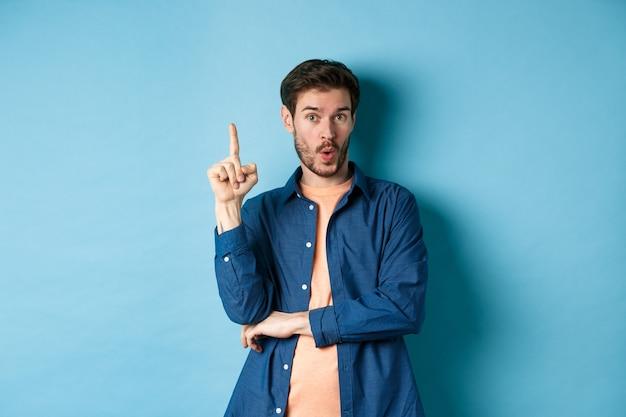 Bel giovane con un'idea, piano di lancio, alzando il dito e dicendo suggerimento, in piedi su sfondo blu.