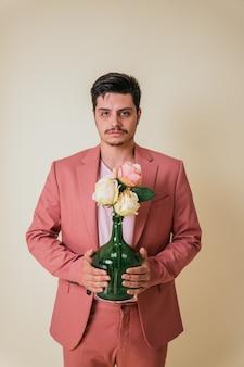 Bel giovane che tiene una bottiglia con fiori vestito con un abito rosa e una maglietta.