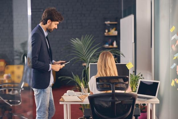Bel giovane che tiene in mano un tablet e guarda una collega mentre lavora al pc desktop