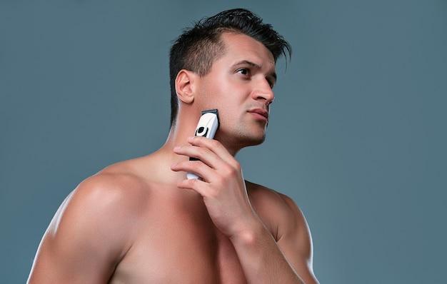 Bel giovane isolato. ritratto di uomo muscoloso senza camicia è in piedi su sfondo grigio con il trimmer in mano durante la rasatura. concetto di cura dell'uomo.